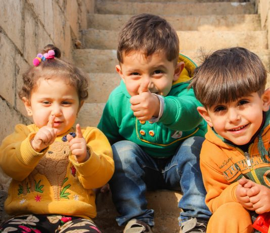 three children from about two to six years old sitting on brownish stairs and laughing